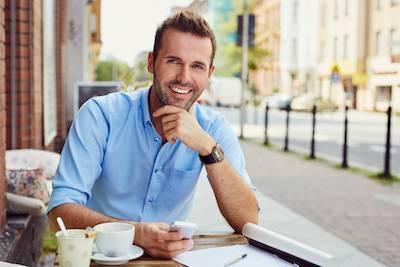 man smiling at outdoor cafe| Fairfax va dentist