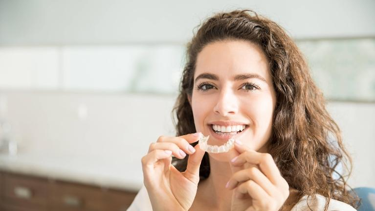 woman holding clear aligners next to her smile